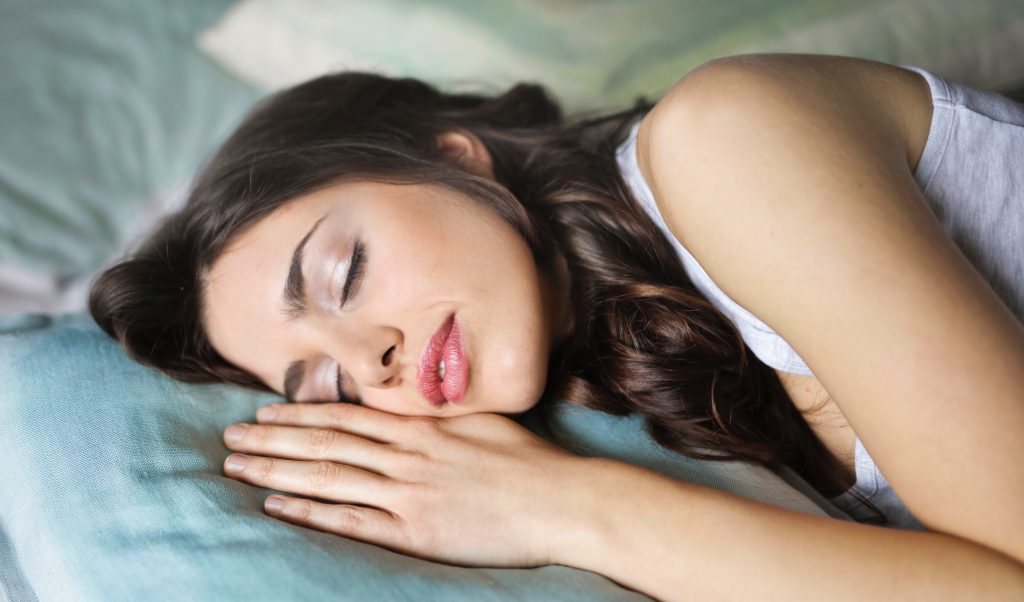 Woman sleeping to achieve a healthy balance of sleep.